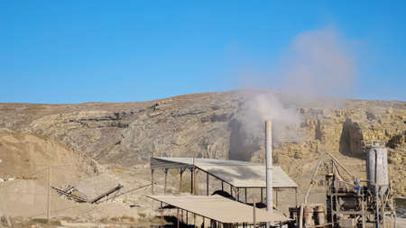 White smoke rises from high chimney on small mining station at large open limestone quarry among hills against blue sky on sunny day