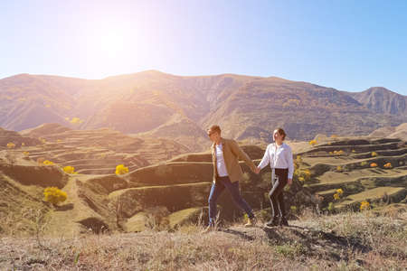 Young couple holding hands is walking on the background of mountain terraces on a sunny day, sunlight