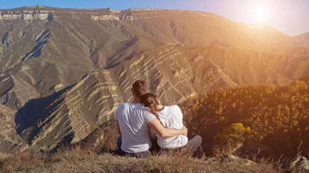 Lovely young man and woman hug sitting on hill edge with dry grass against large ancient mountains and clear blue sky on autumn day. Zdjęcie Seryjne