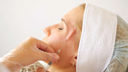 Beautician inserts a long needle with medication under the skin of a womans face.