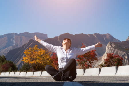 Lady in white hoodie and jeans sits on grey asphalt road stretching arms with joy against colourful trees and rocky mountains at bright sunlight