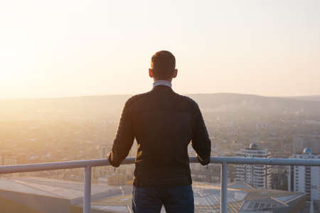 Muscular man in black jacket holds hands on grey metal handrails and admires sunrise over cityscape and hills silhouettes backside view