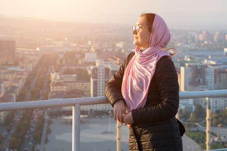 woman with glasses and a pink shawl on the roof of a multi-storey building overlooking the city, sunlight.