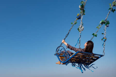 Barefoot brunette in long polka dot dress sits on large designed swings decorated with green leaves and coloured tapes under blue sky