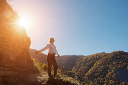 Young woman silhouette stands on hill top against green mountainous forests and large rock at back bright autumn sunlight of orange colour