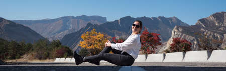 Young woman in white hoodie and sunglasses sits on grey asphalt road barrier against red and orange trees and rocky mountains on autumn day