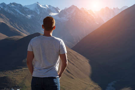 Muscular guy in t-shirt stands and looks at brown rocky mountains with white snowy peaks at back bright autumn sunlight backside view