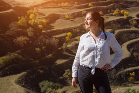 Brunette in white blouse and black jeans poses for camera standing against terraced hill with fields and yellow trees under bright autumn sunlight Zdjęcie Seryjne