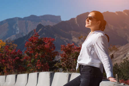 Young woman in sunglasses poses near concrete road barriers against orange yellow autumn trees and rocky hills silhouettes under blue sky Zdjęcie Seryjne