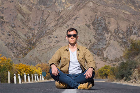 Serious guy in sunglasses poses for camera sitting on empty grey asphalt road between colourful trees against large brown bare mountain in autumn Zdjęcie Seryjne
