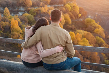 Guy and long haired lady hug sitting on large log at brown wooden handrails against hilly landscape with orange forest trees backside view