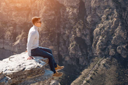 Excited guy in sunglasses and white pullover sits on dangerous edge of large grey rock against brown cliffs under bright autumn sunlight