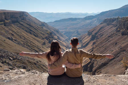Excited couple in hoodies sits on rocky cliff edge stretching hands against deep canyon among mountains under bright sunlight backside view