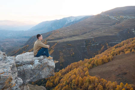 Guy in brown shirt and blue jeans sits on large hilltop rock edge against orange yellow forests and fields of mountainous landscape Zdjęcie Seryjne