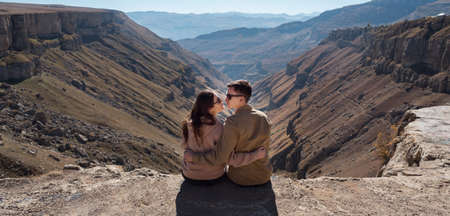 Panorama of romantic couple in love hugs and looks into eyes wearing sunglasses and sitting on steep cliff edge against mountain landscape Zdjęcie Seryjne