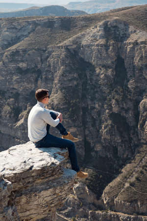 Guy in denim jeans and white shirt sits on edge of steep rocky cliff against large brown bare mountains under sunlight on autumn day.