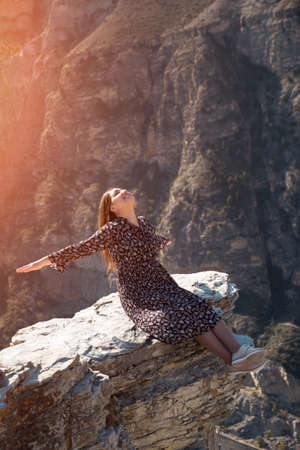 Excited lady with long loose flowing hair sits smiling on dangerous grey rock hilltop edge against steep mountains under bright autumn sunlight