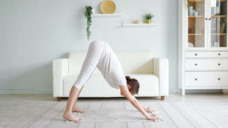 Pretty young pregnant woman does adho mukha svanasana practicing yoga pose on floor mat near sofa in spacious room at home side view Zdjęcie Seryjne