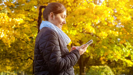 young woman in a black jacket and a gray scarf is typing a message on the phone against the background of yellowed trees copyspace