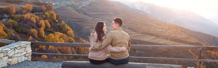 Romantic couple in love kisses and hugs sitting on large log of observation deck against sunrise over rocky hills and orange forests backside view