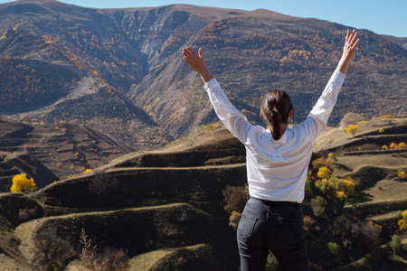 Young woman in white shirt enjoying the view of the valley with her arms spread, rear view. Imagens - 162162434