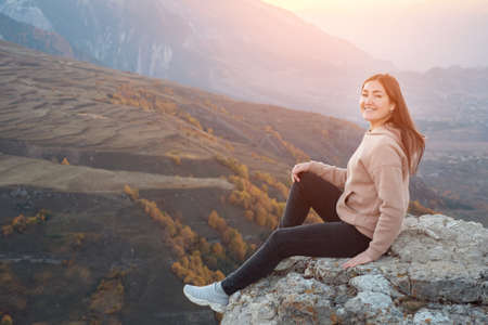 Young woman with long loose hair sits posing and smiling on high rocky hill top edge of grey colour against forestry landscape lit by sunlight