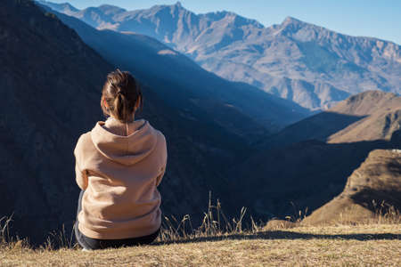 Young woman in a hoodie sits on the ground against a background of mountains, back view.