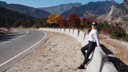 Young woman in black jeans and white hoodie stands near mountain road barrier against coloured autumn trees and hilly landscape under blue sky