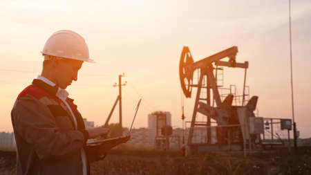 man in a white helmet with a laptop on the background of an oil rocking at sunset. Imagens