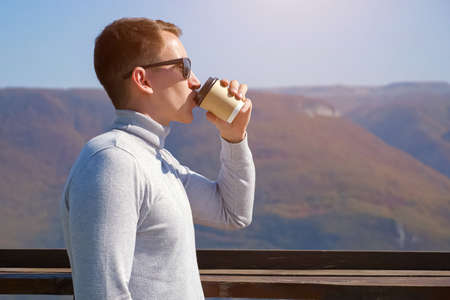 Young guy drinks coffee against mountains on a clear day, sunlight 스톡 콘텐츠