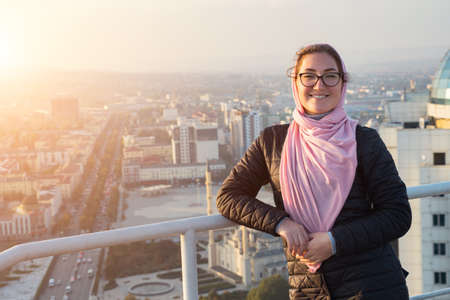 Young woman wearing glasses and a pink shawl on the roof of a high-rise building with a city view.