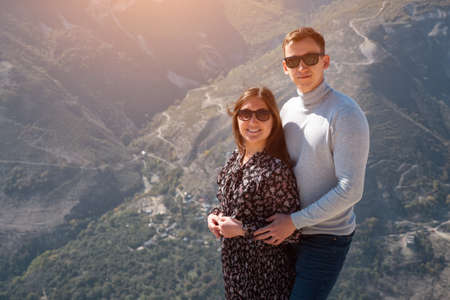 Romantic couple in sunglasses poses on hilltop over canyon against hilly landscape with green forests and thin paths under bright autumn sunlight 스톡 콘텐츠
