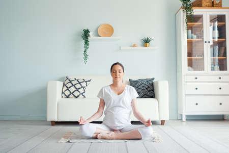 Smiling young pregnant lady in white meditates sitting in padmasana yoga position on floor against designer furniture in spacious room at home 스톡 콘텐츠