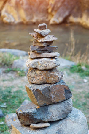 Close-up of a pyramid of stones on the background of the river and rocks.