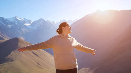 Happy woman wearing sunglasses and pink hoodie enjoys bright sunshine rays standing against amazing mountain range peaks