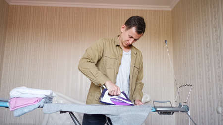 Concentrated man wearing brown shirt does chores and irons clothes after laundry using purple electric iron on special board close view 스톡 콘텐츠