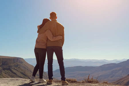 Young couple in love over the cliff admire the view of the valley on a clear sunny day, copyspace