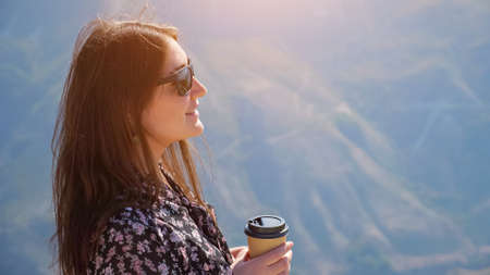 Brunette woman with stylish sunglasses in color dress drinks coffee enjoying wonderful landscape of hilly valley at highland on sunny day closeup