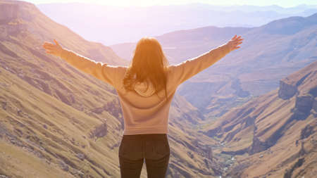 Brunette woman spreads her arms to the sides against the background of a river valley, sunlight