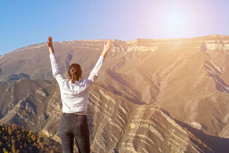 Young woman in white shirt walks and raises hands on hill edge against distant ancient mountains and clear blue sky backside view