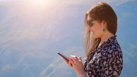 Young woman with phone against the background of mountains on a sunny day, hair fluttering in the wind.