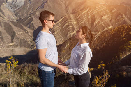 man and a woman stand opposite each other holding hands on the background of mountains, sunlight.