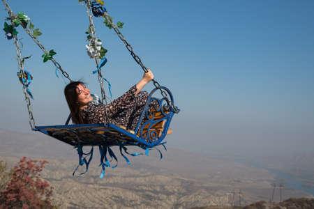 Brunette woman swinging on a swing in the mountains, copyspace