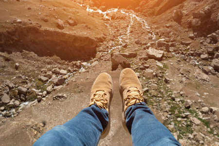 Mans legs over a cliff and a mountain river, sunlight.