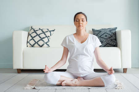 Smiling young pregnant woman in white meditates sitting in yoga position on floor at home closeup
