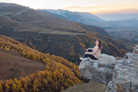 Young woman in brown hoodie sits on large rock top edge of hill against mountainous landscape with orange trees and fields in autumn