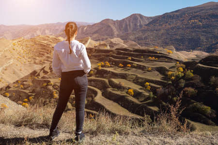 Brunette in white blouse and black denim jeans stands on brown hill top admiring hilly landscape with terraced fields and trees backside view