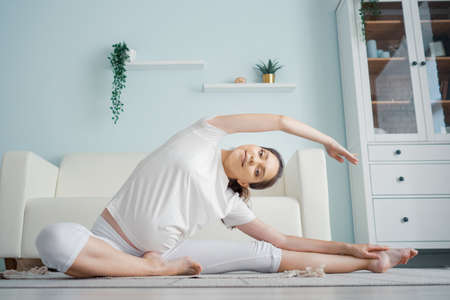 Attractive pregnant lady in white clothes does janu sirsasana position sitting on floor with rug against designer couch in spacious room at home 스톡 콘텐츠