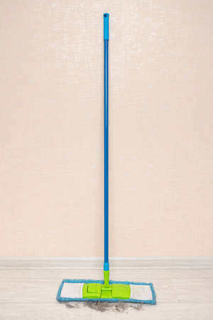 blue mop stands against a wall with collected trash on the floor.