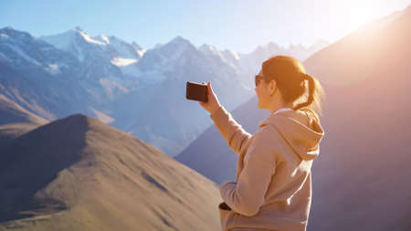 Young woman takes pictures on the phone of a beautiful mountain landscape with snow-capped mountain peaks.